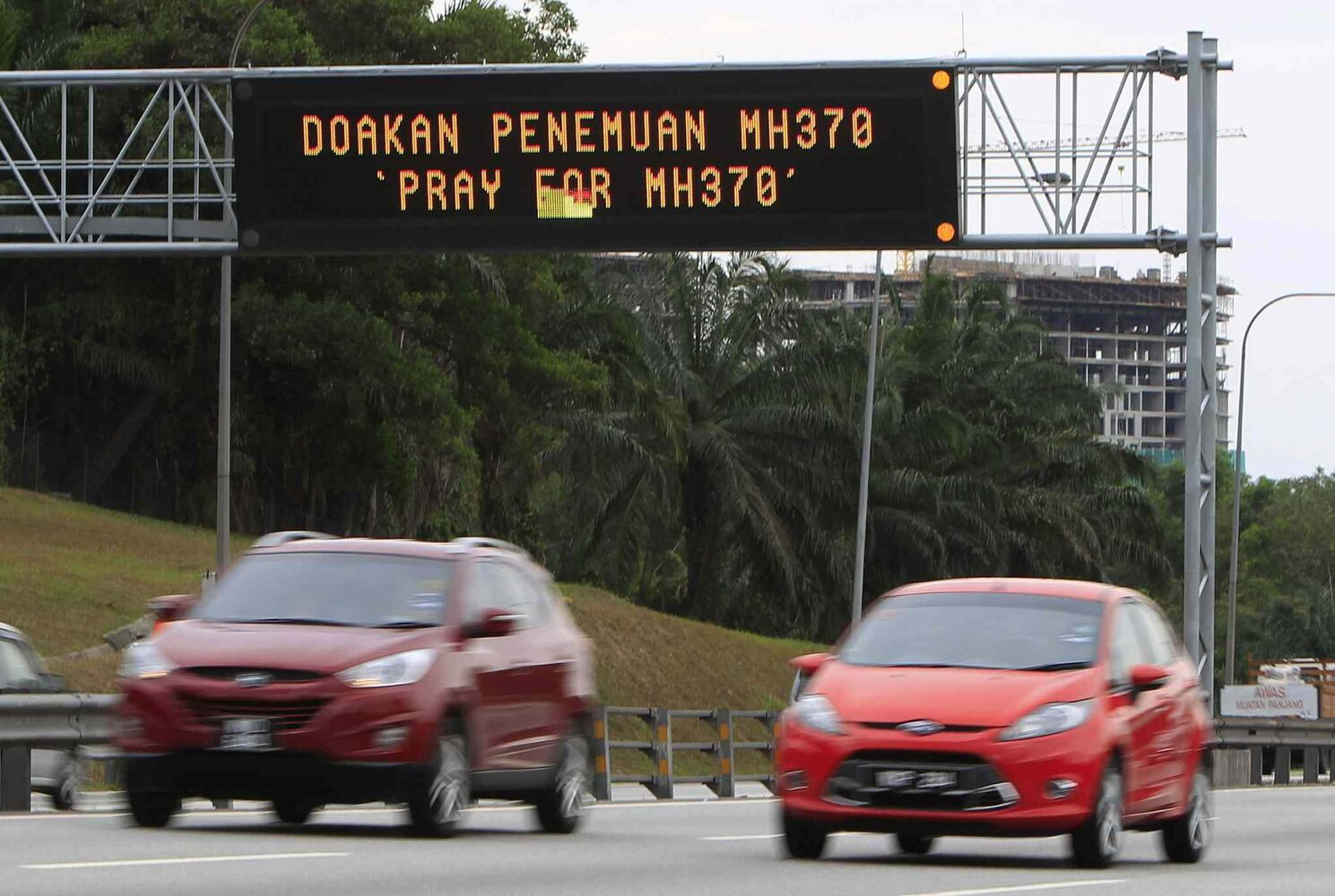 "Motorists drive past an electronic board displaying ""Pray for MH370"" in Shah Alam, outside Kuala Lumpur, Malaysia, Sunday, March 16, 2014. Malaysian authorities Sunday were investigating the pilots of the missing jetliner after it was established that whoever flew off with the Boeing 777 had intimate knowledge of the cockpit and knew how to avoid detection when navigating around Asia. (CP)"