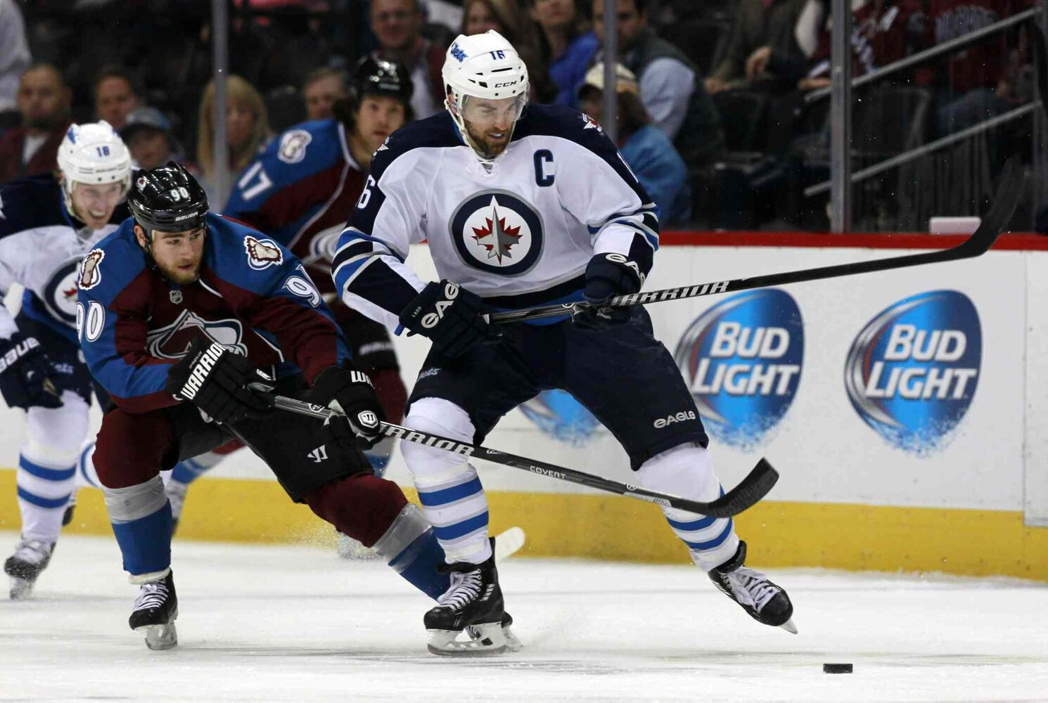 Andrew Ladd (right) is hooked by Colorado Avalanche centre Ryan O'Reilly while reaching for the puck in the first period. (David Zalubowski / The Associated Press)