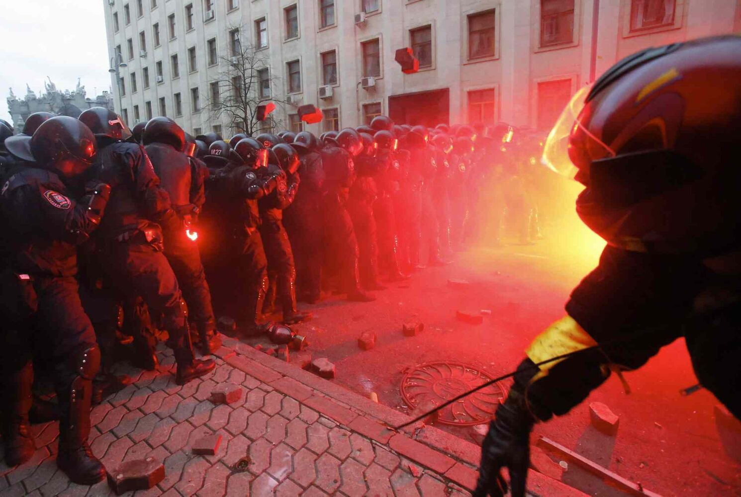 Protesters throw stones as they clash with police outside the presidential administration building in downtown Kiev, Ukraine. More than 100,000 demonstrators chased away police to rally in the center of Ukraine's capital on Sunday.  (Sergei Grits / The Associated Press)