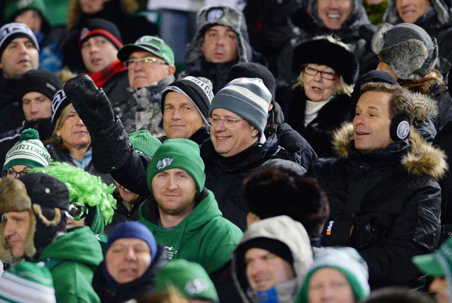 Prime Minister Stephen Harper (centre, in striped toque), sits with CFL Commissioner Mark Cohon (right) during the third quarter. (Liam Richards / The Canadian Press)