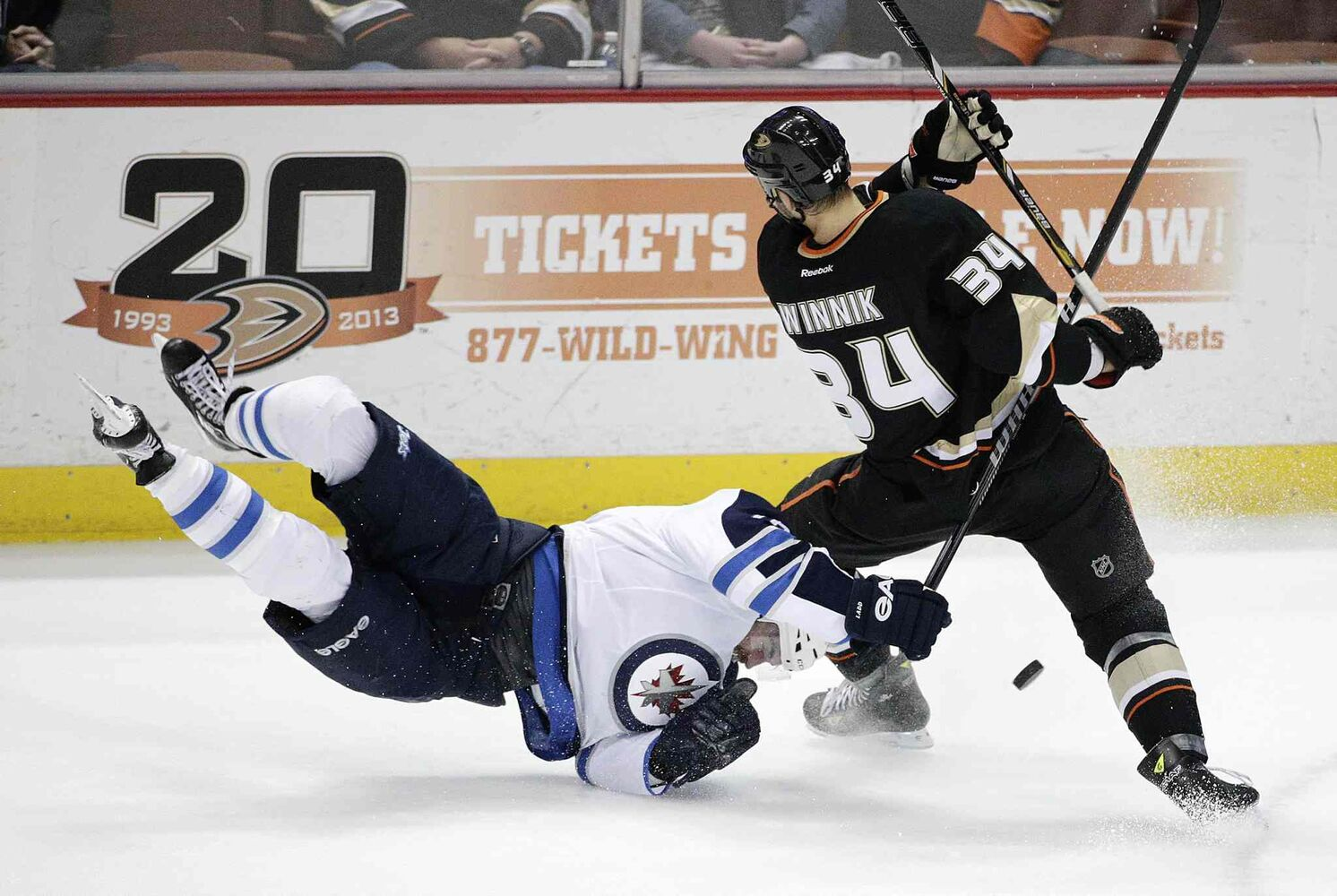 Winnipeg Jets' Andrew Ladd, left, falls to the ice while fighting for the puck with Anaheim Ducks' Daniel Winnik during first period. (Jae C. Hong / The Associated Press)