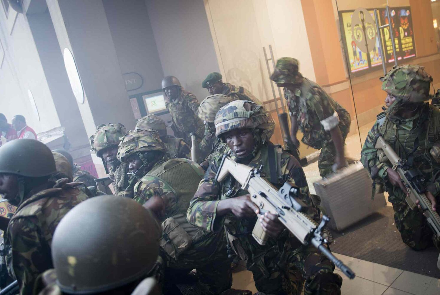 Armed police leave after entering the Westgate Mall in Nairobi, Kenya Saturday, Sept. 21, 2013. Gunmen threw grenades and opened fire Saturday, killing at least 22 people in an attack targeting non-Muslims at an upscale mall in Kenya's capital that was hosting a children's day event.