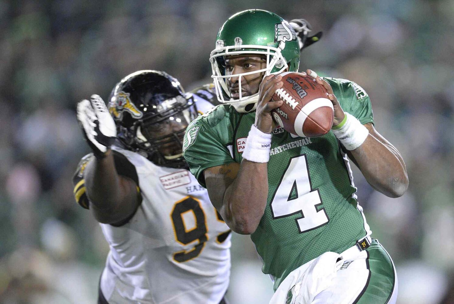 Saskatchewan Roughriders quarterback Darian Durant (right) runs with the ball as he is rushed by Hamilton Tiger-Cats defensive lineman Torrey Davis during the fourth quarter. (CP)
