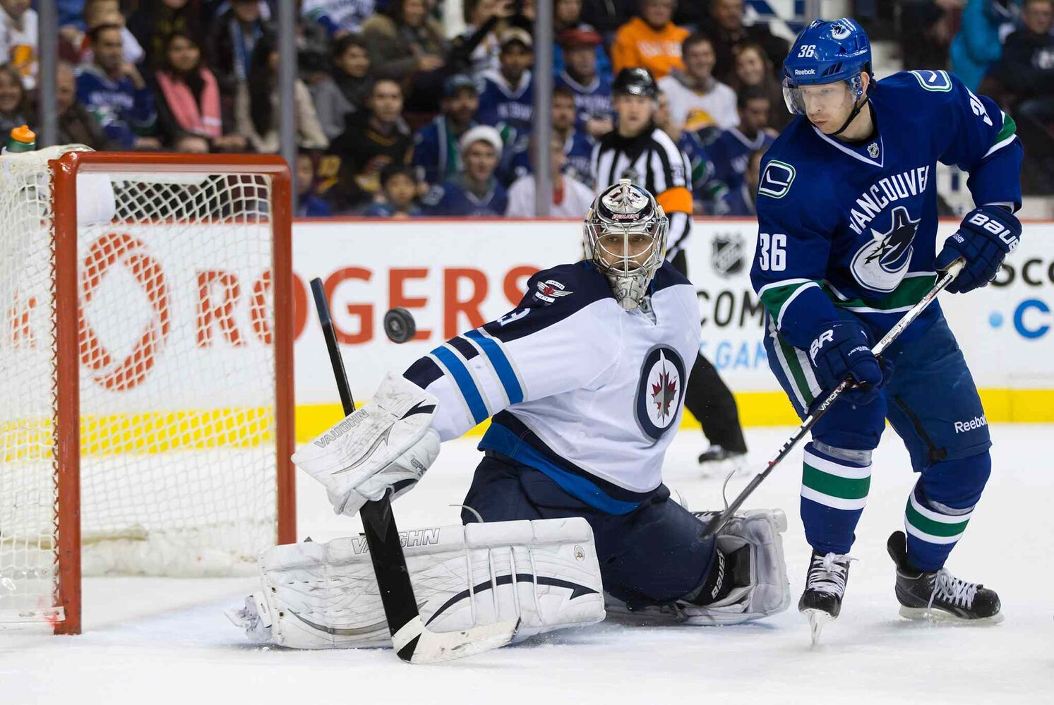 Jannik Hansen (right) of the Vancouver Canucks tips the puck wide of Winnipeg Jets goalie Ondrej Pavelec.