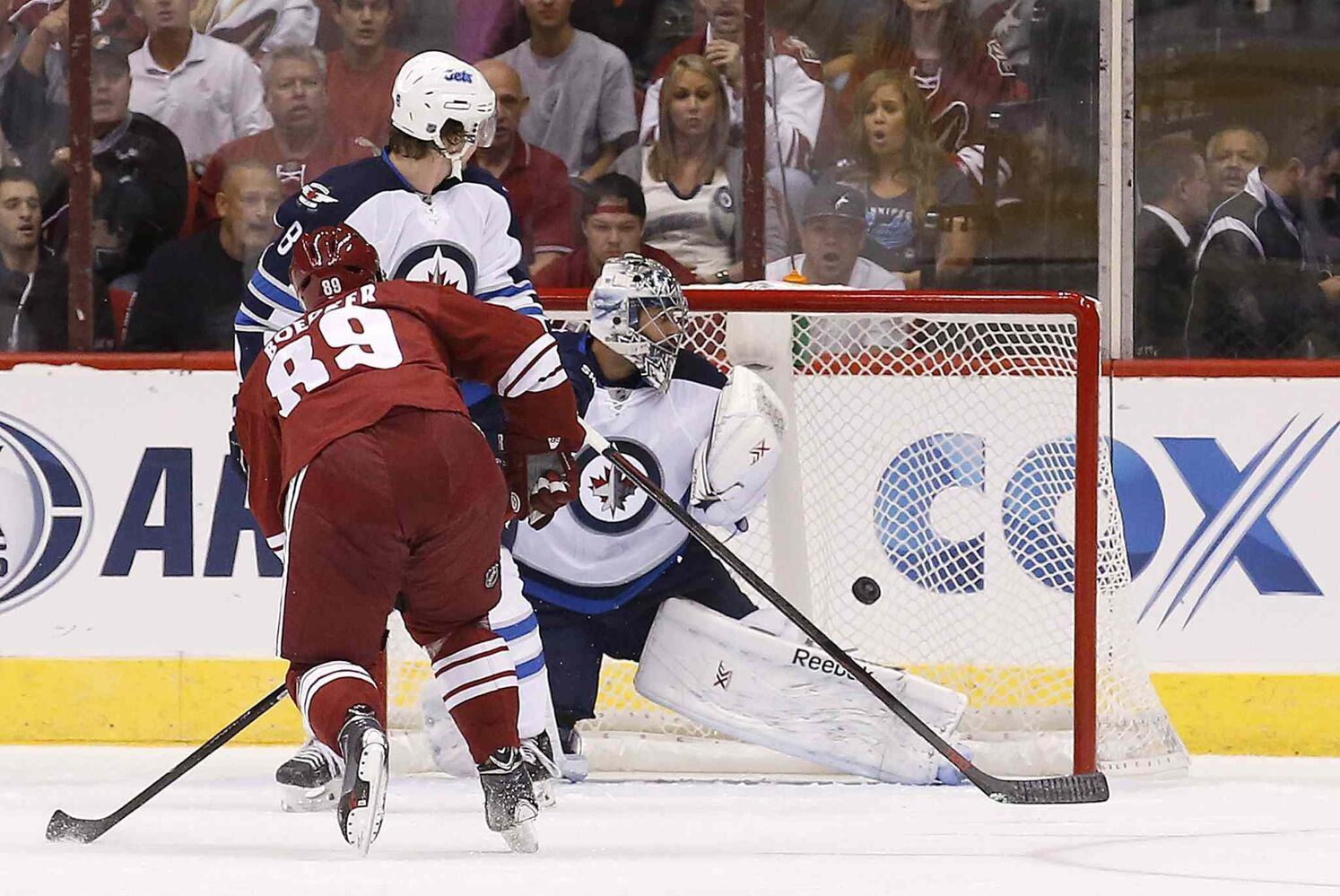 Arizona Coyotes' Mikkel Boedker (89), of Denmark, scores a goal against Winnipeg Jets' Ondrej Pavelec, right, of the Czech Republic, as Jets' Jacob Trouba (8) looks on during the first period of an NHL hockey game Thursday, Oct. 9, 2014, in Glendale, Ariz. (Ross D. Franklin / The Associated Press)