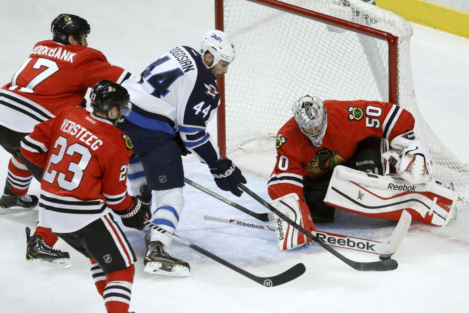 Blackhawks goalie Corey Crawford thwarts Jets defenseman Zach Bogosian's attempt to score. (Charles Rex Arbogast / The Associated Press)