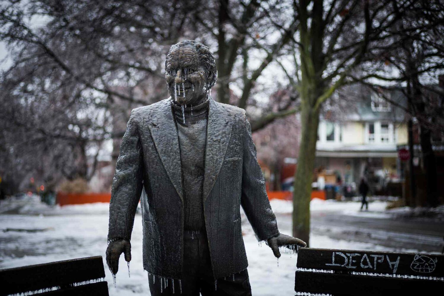 An ice-covered statue of Al Waxman is seen in Toronto's Kensington Market Sunday.
