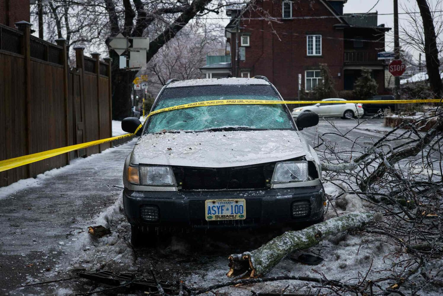 A vehicle that was smashed by a falling tree bow near Dufferin Grove Park is covered in ice in Toronto on Sunday.