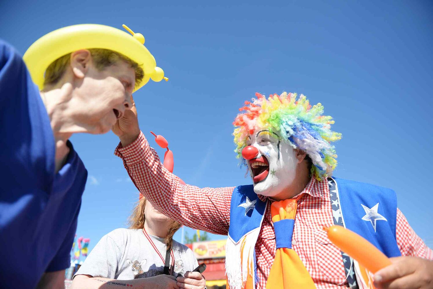 Doo Doo the Clown makes a balloon hat for Sue Fleming on Wednesday. (Sarah Taylor / Winnipeg Free Press)