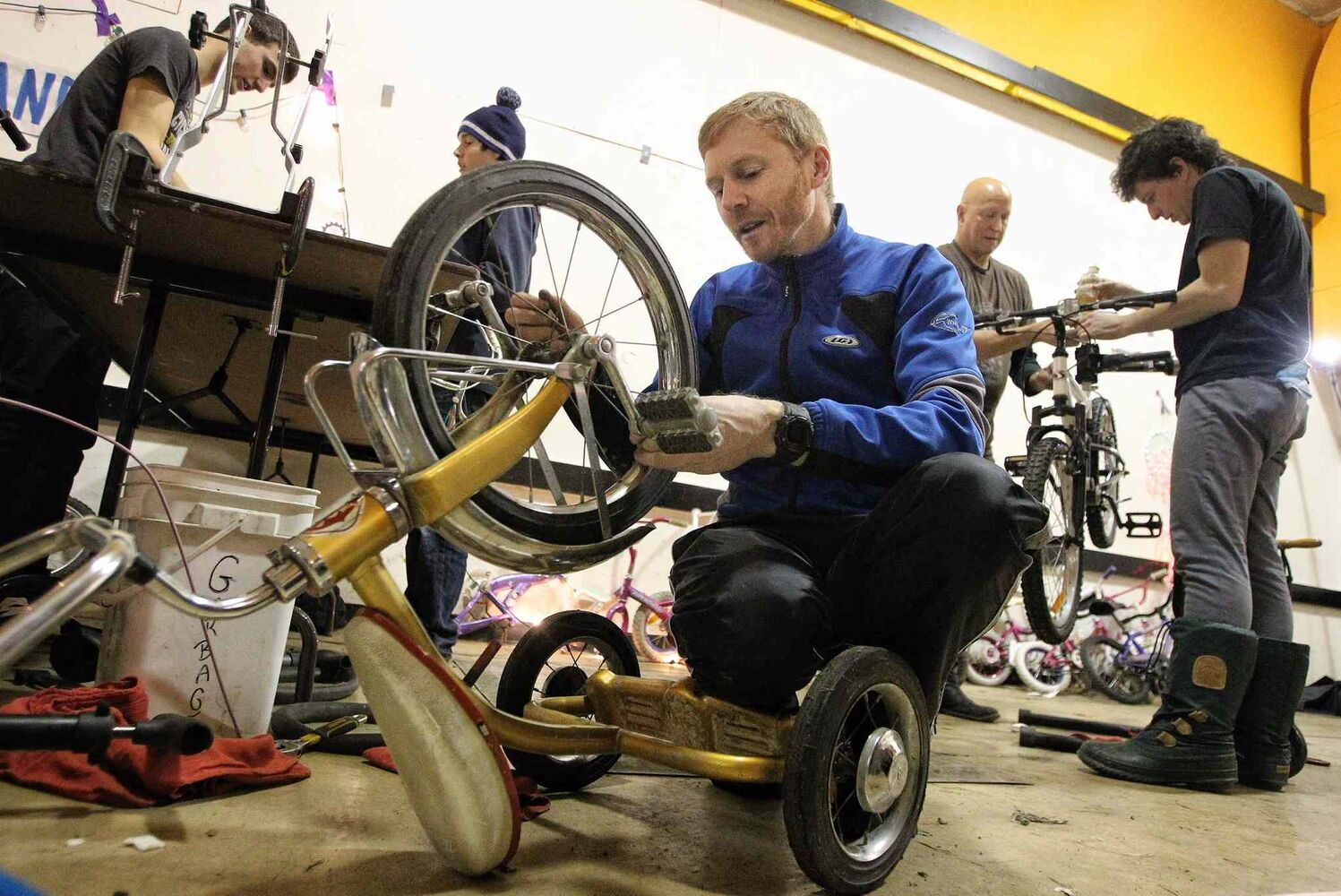 Manitoba provincial cycling team coach Jayson Gillespie works on a tricycle during the Cycle of Giving bike-building marathon. (MIKE DEAL / WINNIPEG FREE PRESS)