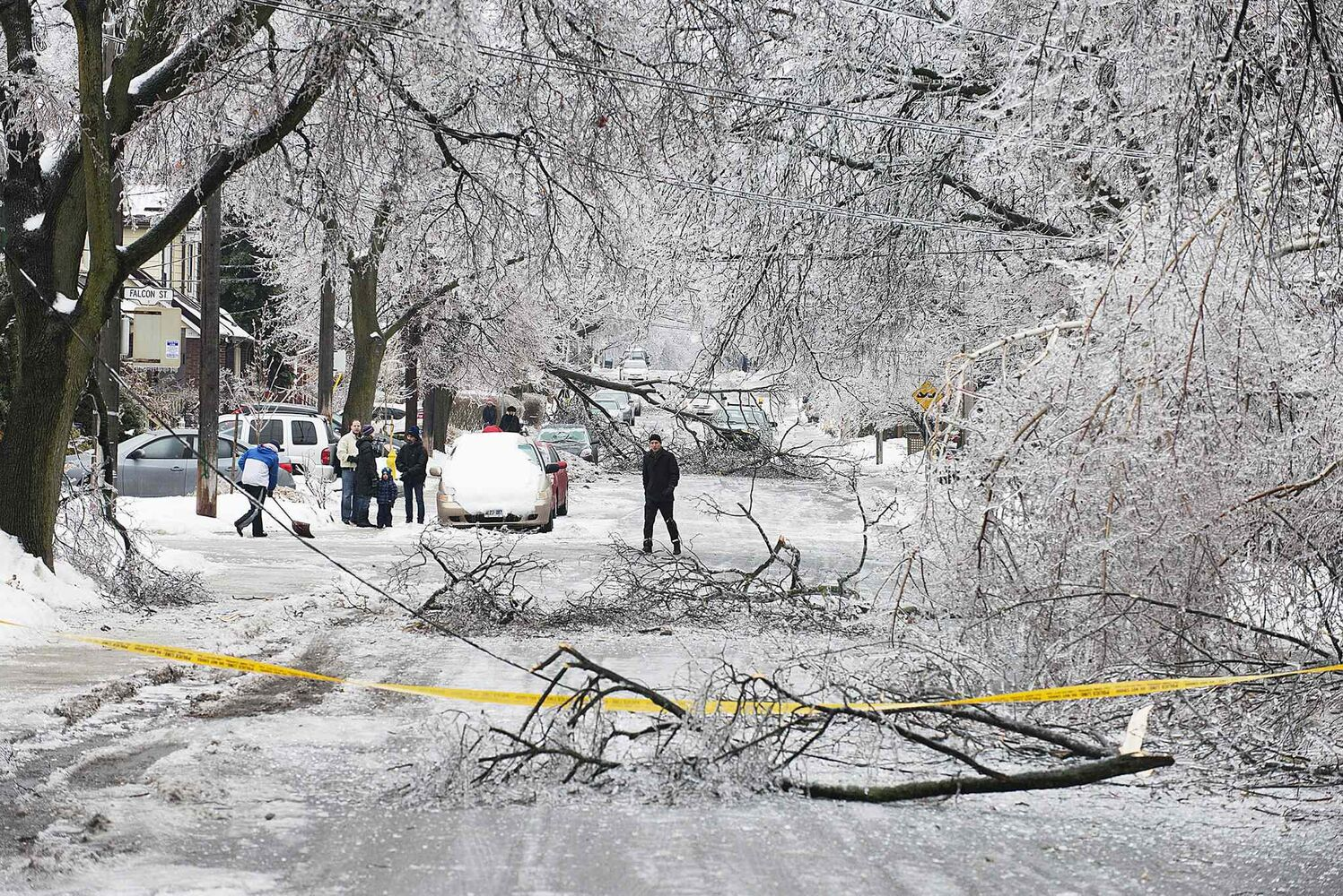 Pedestrians navigate a closed-off Soudan Ave. in Toronto after an ice storm caused havoc, knocking down trees and power lines in much of the city on Sunday.
