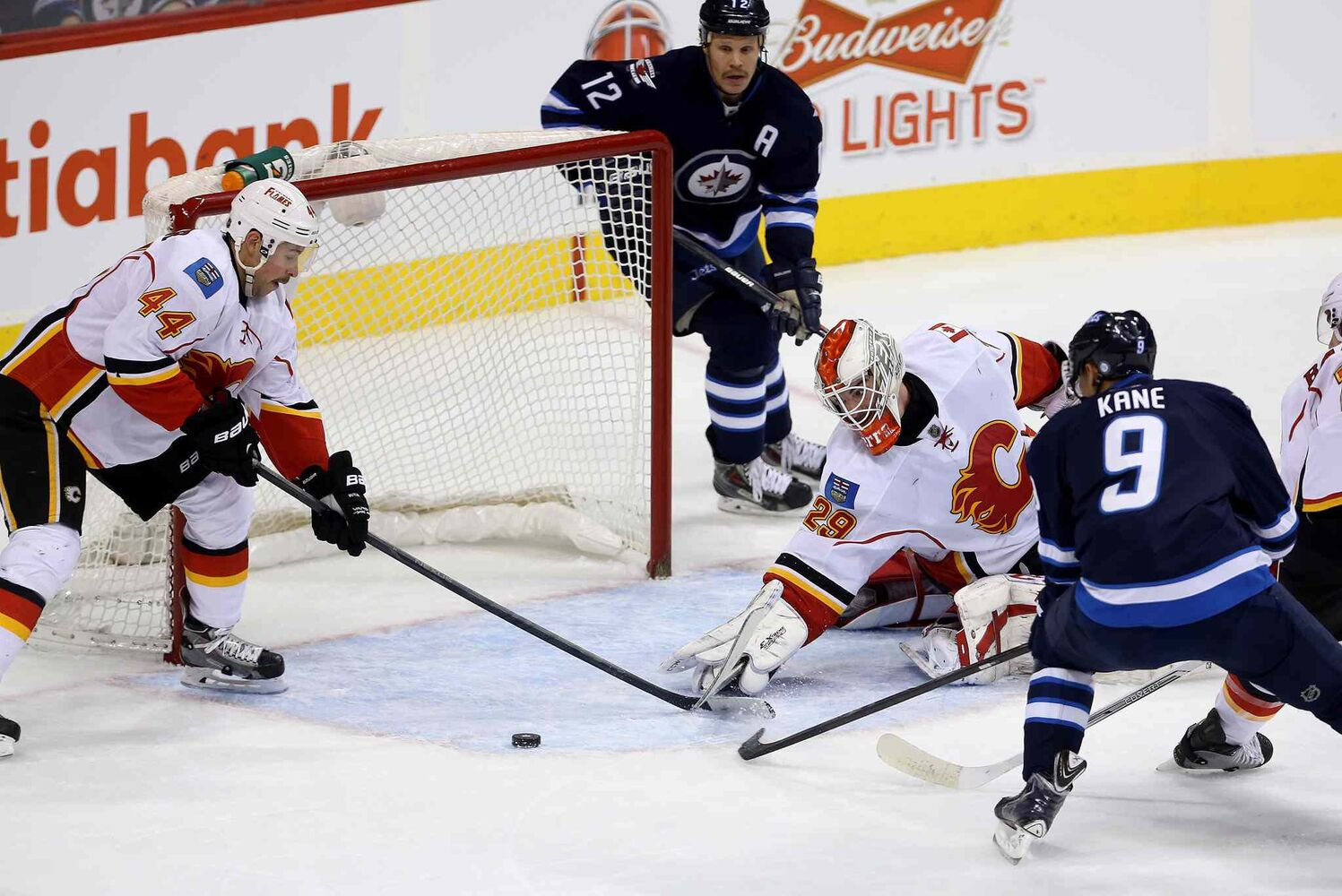 Calgary Flames' Chris Butler (44), goaltender Reto Berra (29) and Winnipeg Jets' Evander Kane (9) all swipe for a free puck in front of the net during first period NHL hockey action in Winnipeg Monday, Nov. 18, 2013.