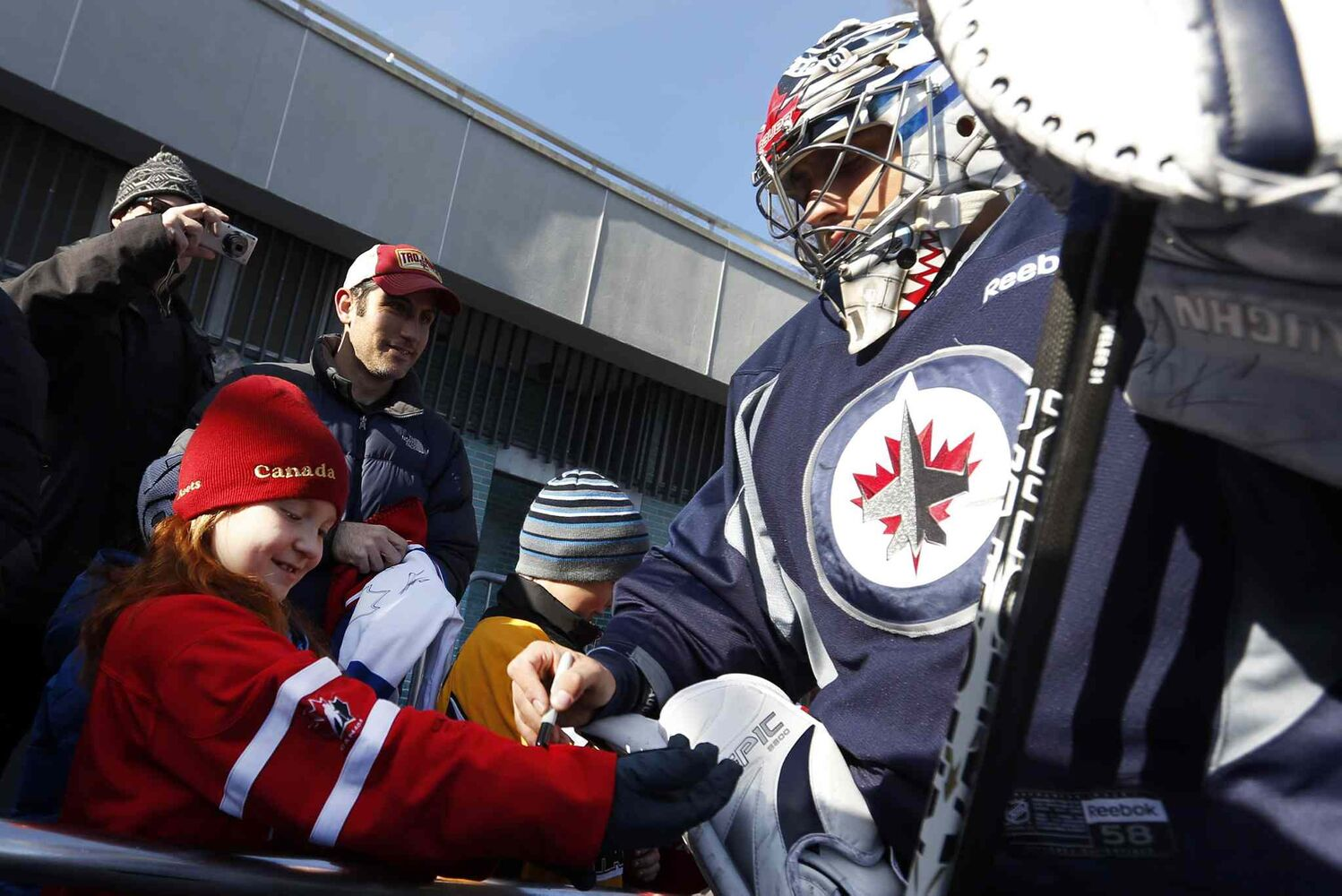 Winnipeg Jets goalie Ondrej Pavelec (right) signs an autograph for fan Alison Giebler, 8, of New York.