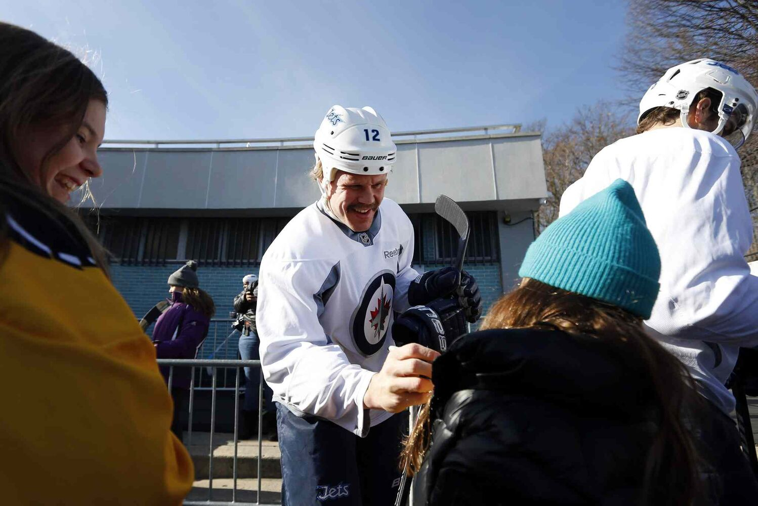 Olli Jokinen signs autographs for a pair of young fans. (Jason DeCrow / The Associated Press)