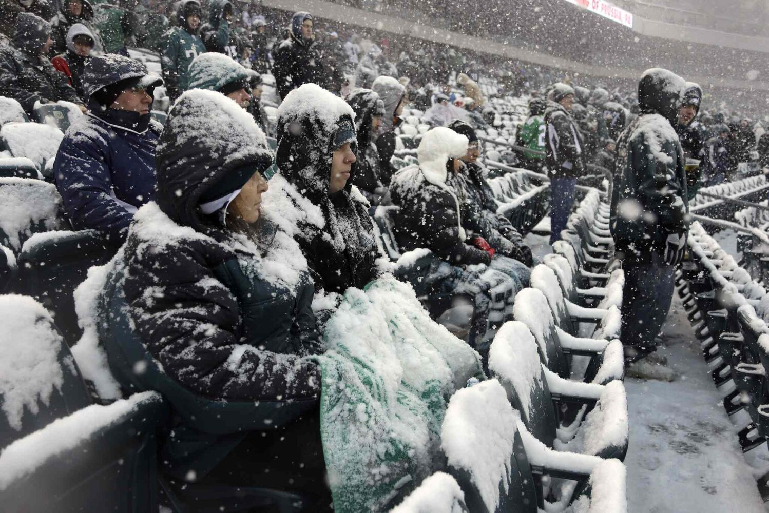 Fans covered with snow wait in the stands before an NFL football game between the Philadelphia Eagles and the Detroit Lions in Philadelphia on Sunday.