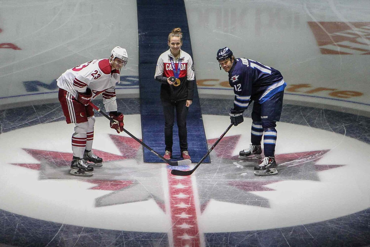 Olympian and gold-medal hockey player Jocelyne Larocque drops the puck for Winnipeg Jets' Olli Jokinen (12) and Phoenix Coyotes' Oliver Ekman-Larsson (23) before the Winnipeg Jets game against the Phoenix Coyotes at MTS Centre Thursday night. (Mike Deal / Winnipeg Free Press)