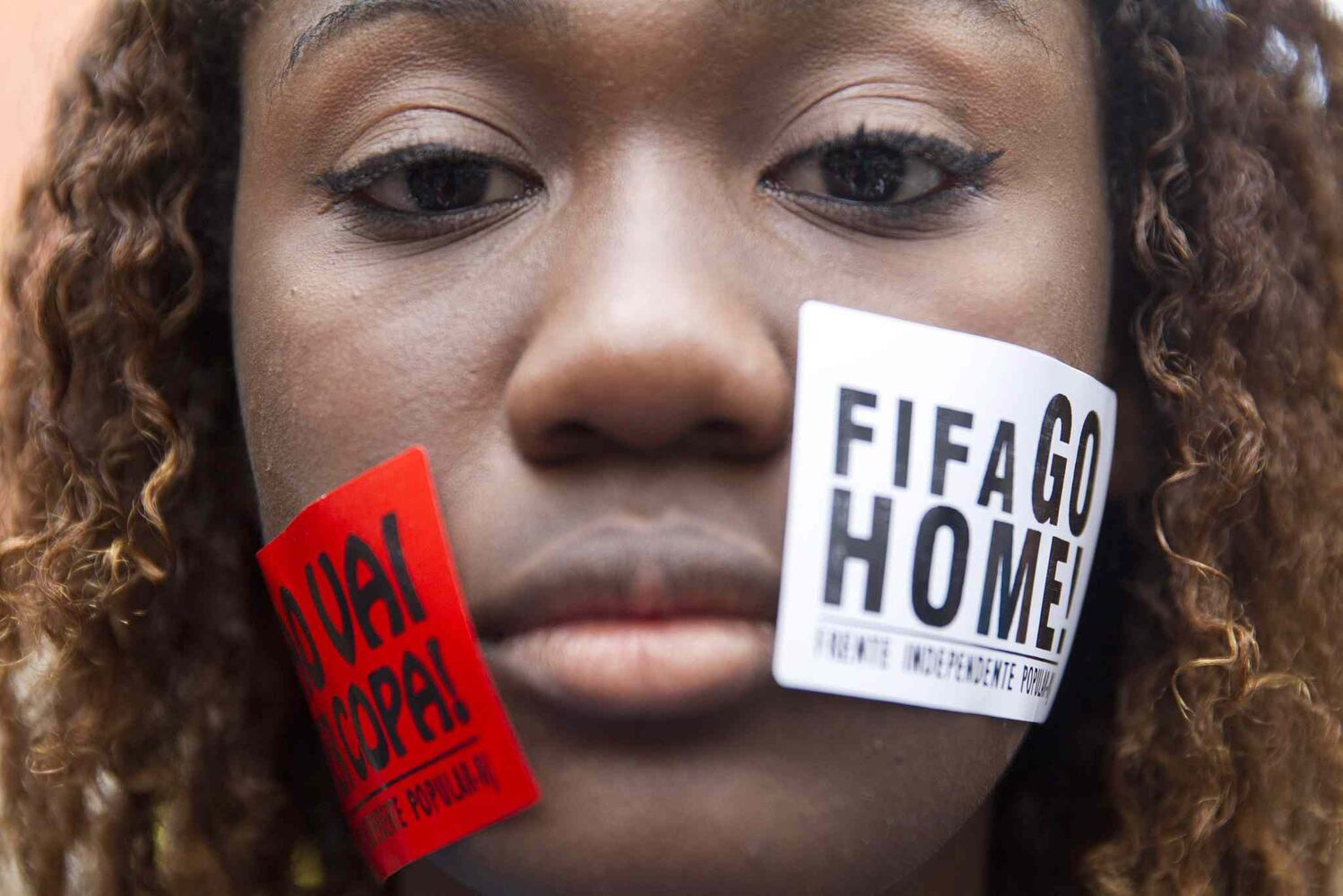 "A woman protests with signs pasted on her face that read ""FIFA Go Home"" and ""Will not have a Cup"" during a march against the World Cup 2014 at the Copacabana beach, in Rio de Janeiro on Thursday.  (Leonardo Wen / The Associated Press)"