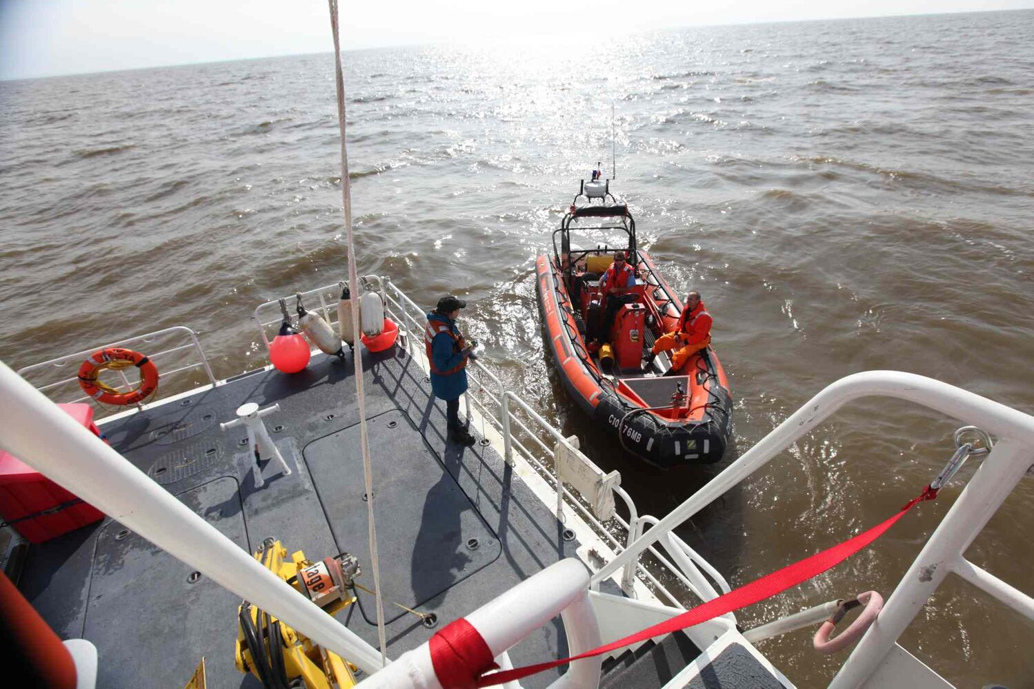 Rescue vessels position themselves alongside each other.