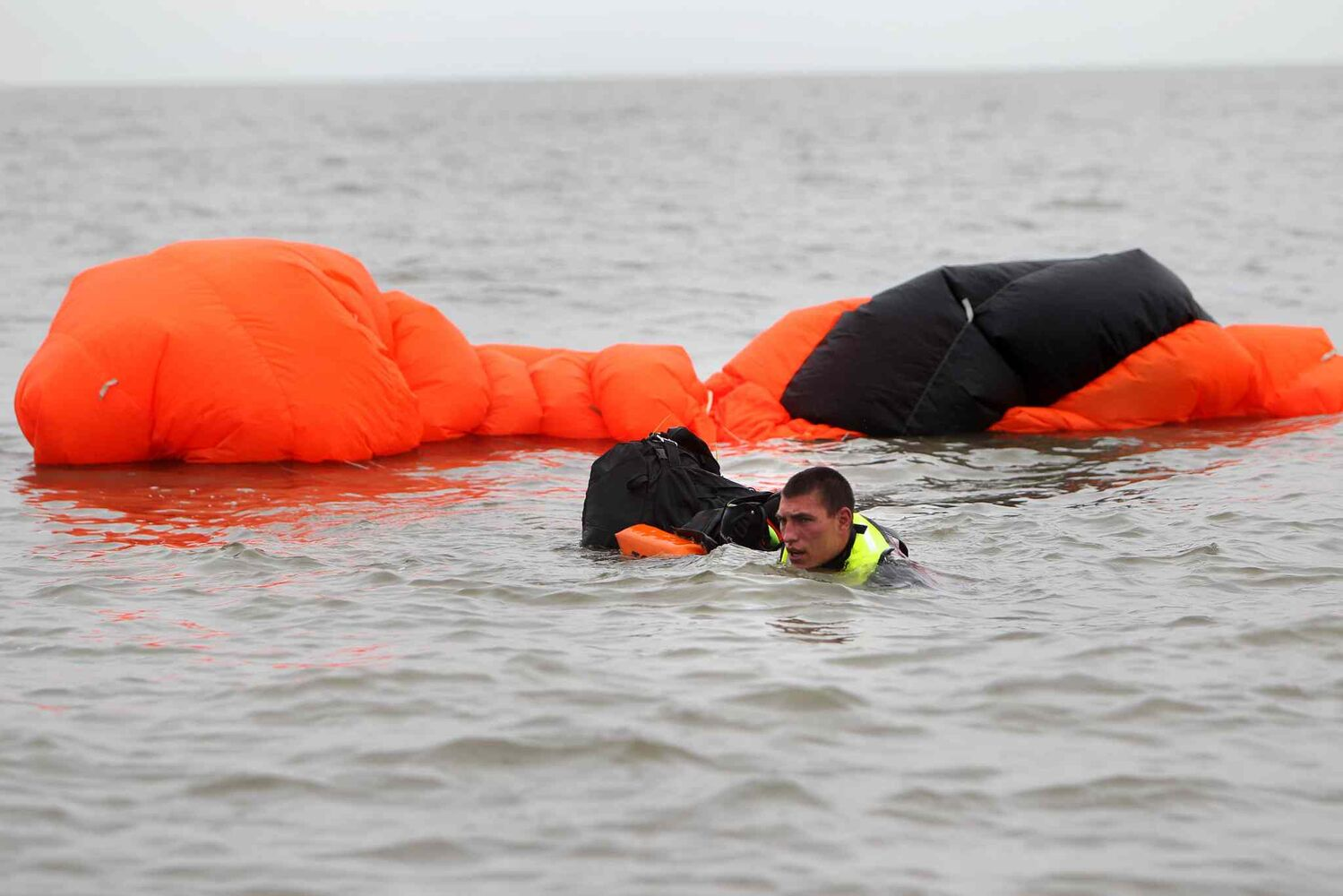 A SAR tech drags rescue gear through the water to the Lady Roberta. (Ruth Bonneville / Winnipeg Free Press)