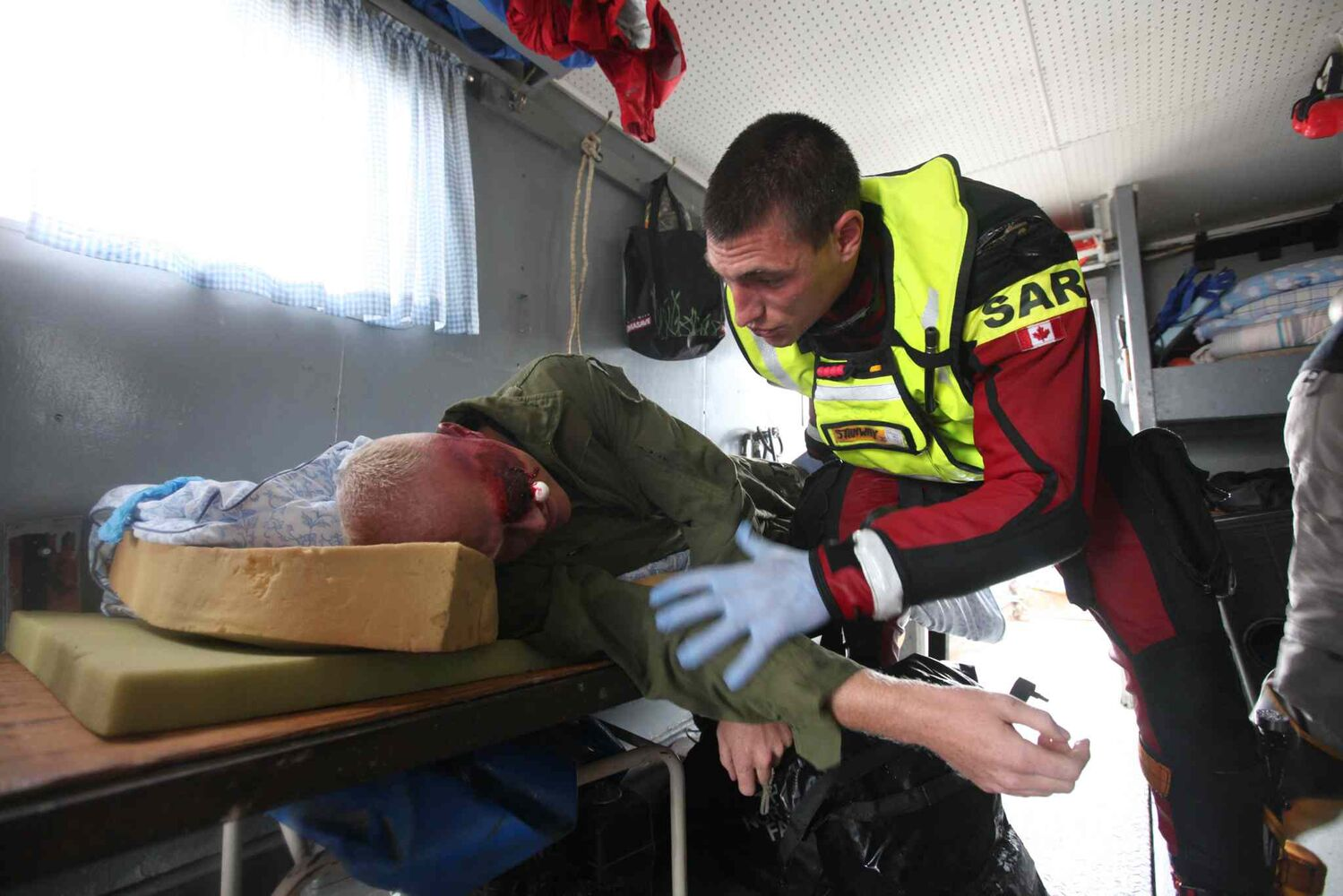 A SAR tech responder tends to a trauma victim aboard the Lady Roberta. (Ruth Bonneville / Winnipeg Free Press)