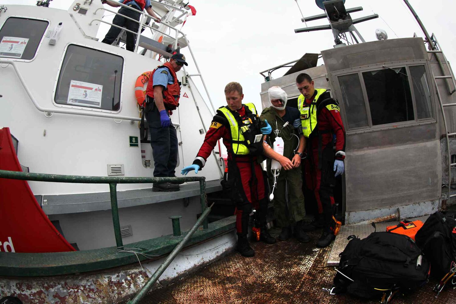 SAR techs help the victim out to the deck of the ship.