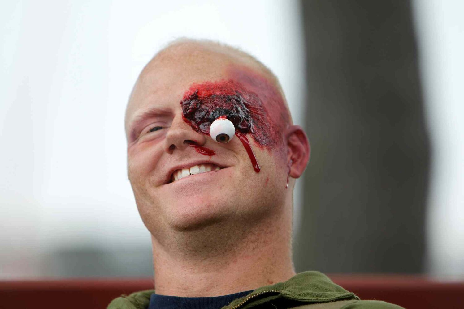 Captain James Grey of Cold Lake, Alta., grins despite his seemingly grim situation. Makeup and prosthetics were applied to give his 'injury' a life-like feel. (Ruth Bonneville / Winnipeg Free Press)