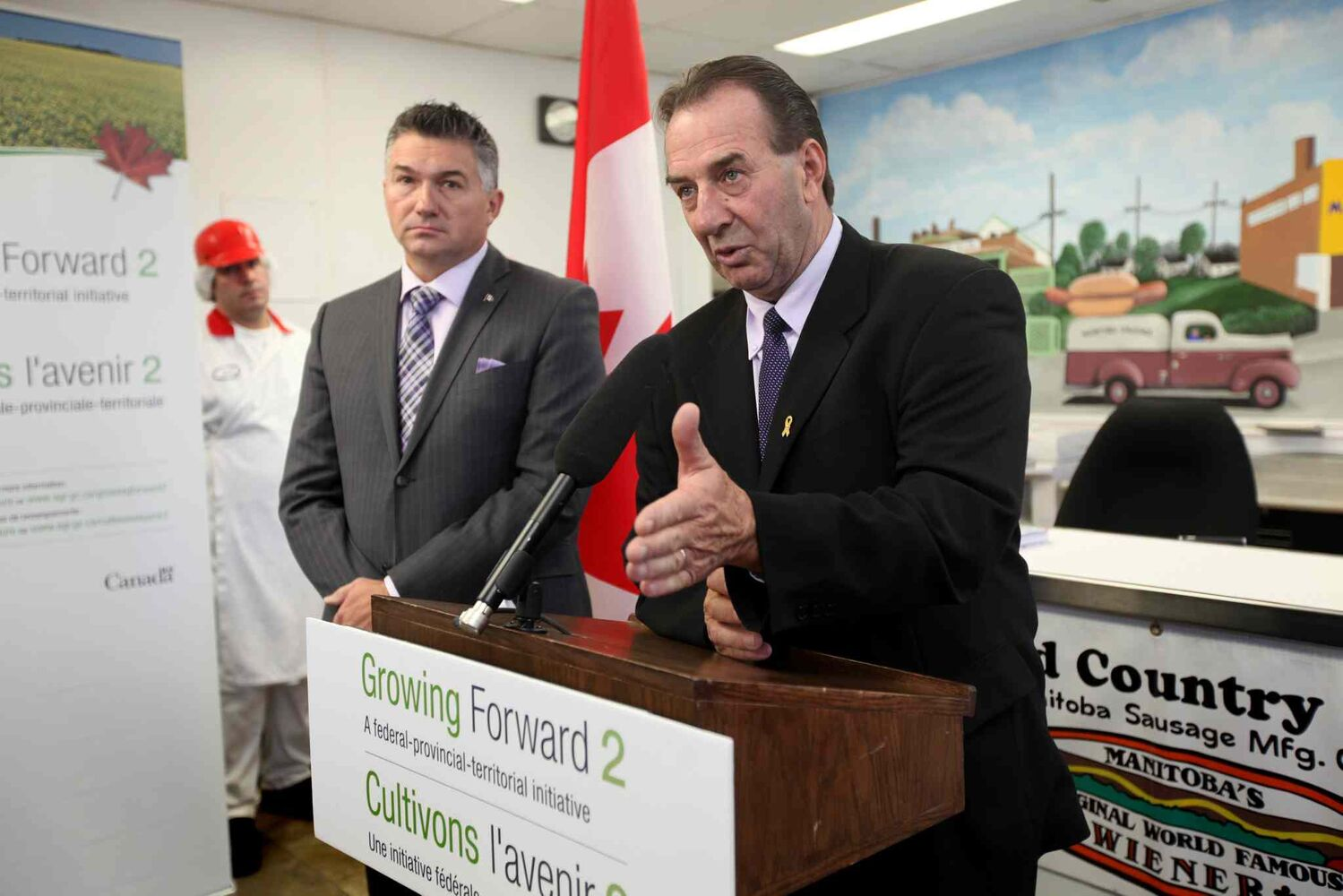 Minister of Agriculture, Food and Rural Initiatives Ron Kostyshyn (right) and Selkirk-Interlake MP James Bezan speak at a press conference Wednesday morning at Winnipeg Old Country Sausage factory on Dufferin Ave. (Ruth Bonneville / Winnipeg Free Press)