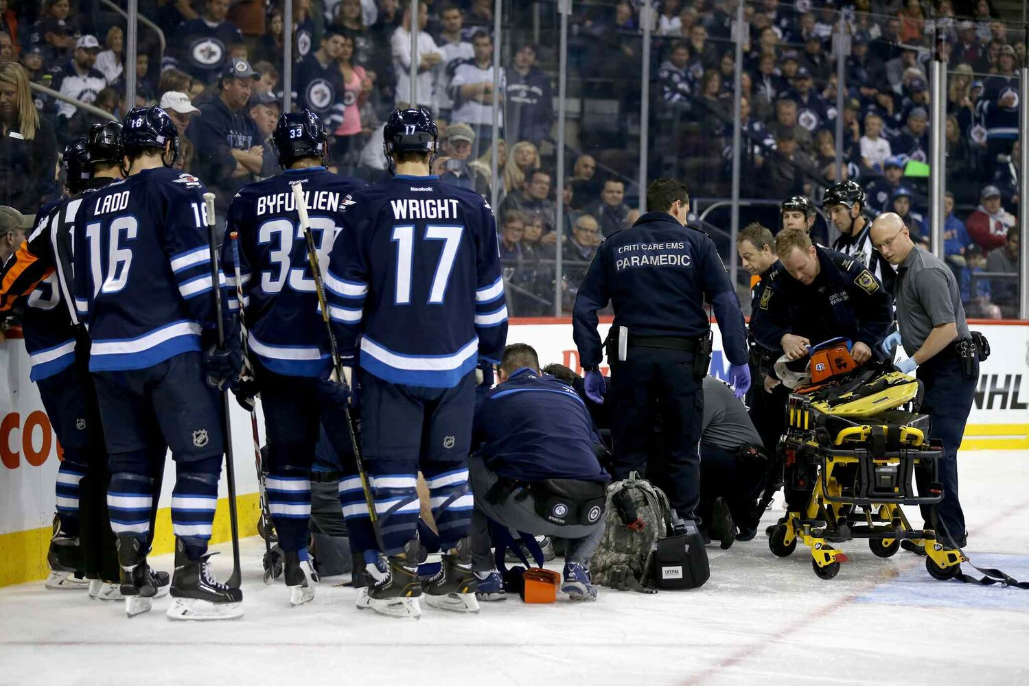 Winnipeg Jets defenceman Jacob Trouba lays on the ice as he is tended to by emergency personnel after going hard into the boards head first in the second period. (TREVOR HAGAN / WINNIPEG FREE PRESS)