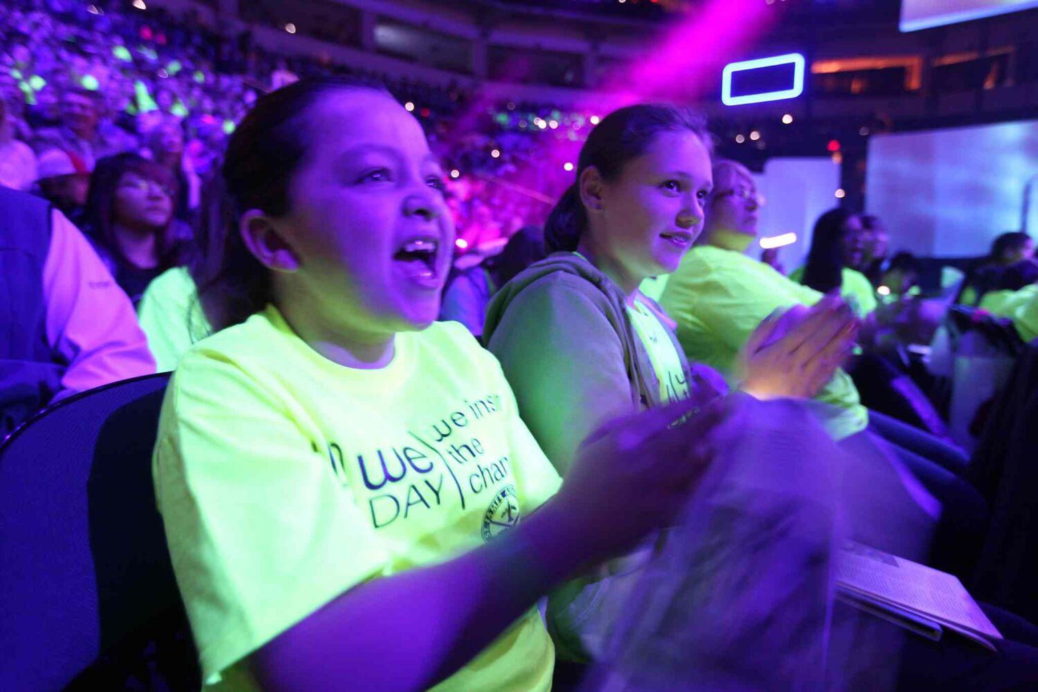 Caitie McHugh (front) and Brynn McGinnis of Lincoln School scream with excitement during We Day.