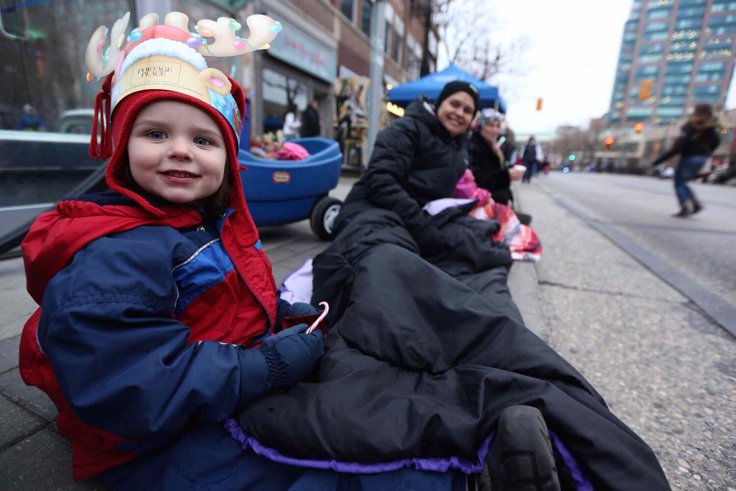 Four-year-old Madeline Dunton and her mom Sally wait along Portage Avenue for the parade to begin. (TREVOR HAGAN / WINNIPEG FREE PRESS)