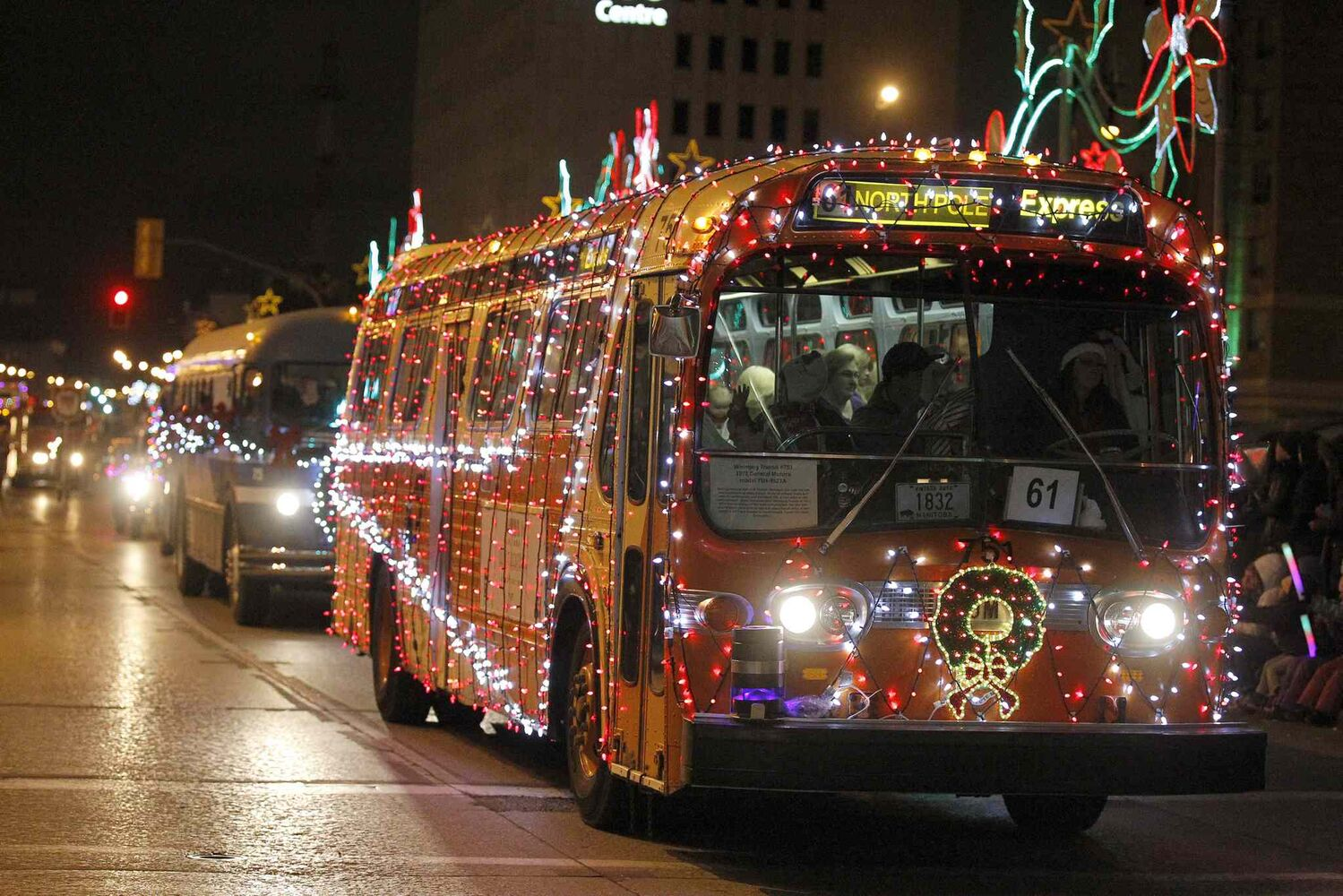 An old Winnipeg Transit bus is covered in lights as part of the parade.