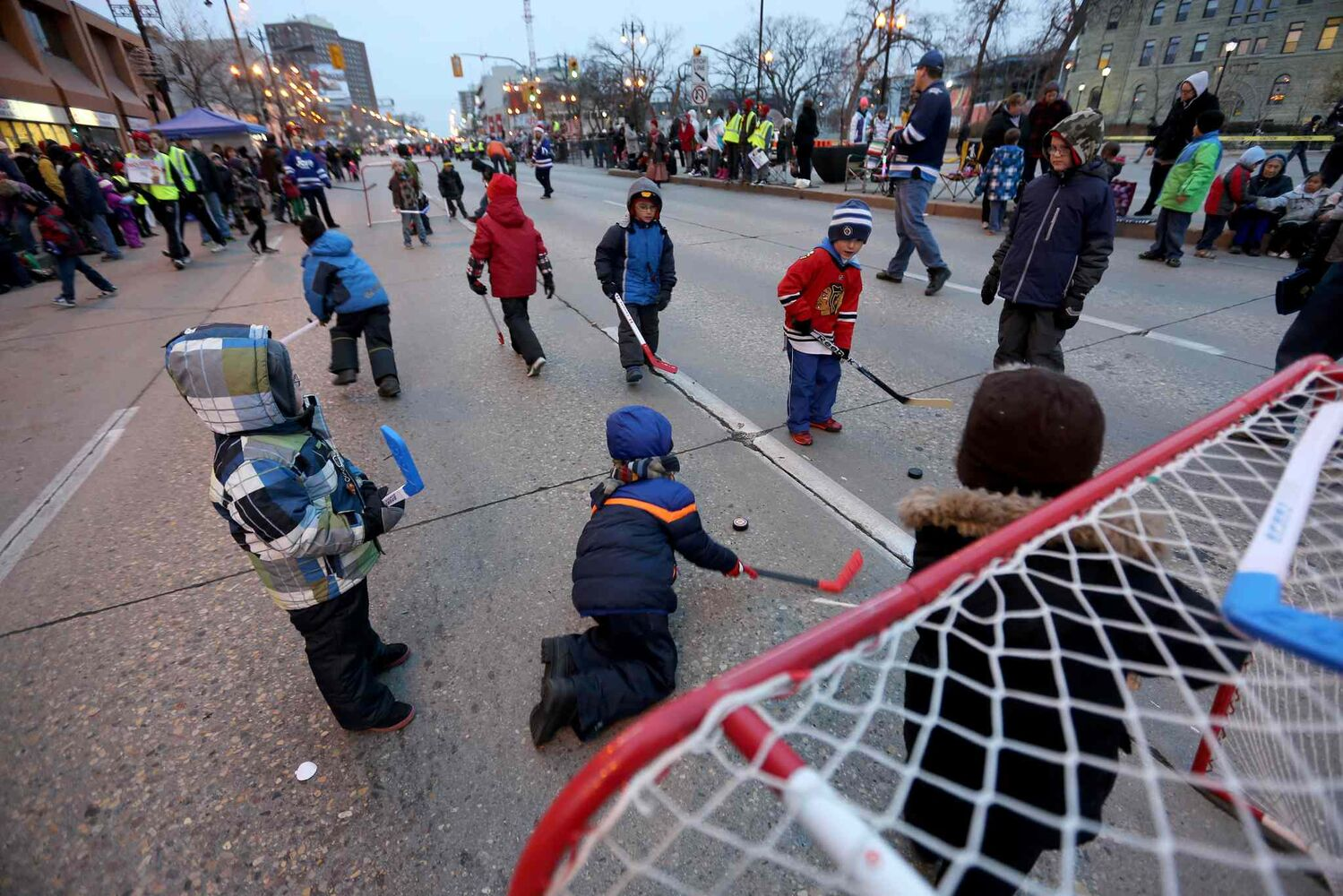 A game of street hockey before the parade keeps kids busy. (TREVOR HAGAN / WINNIPEG FREE PRESS)