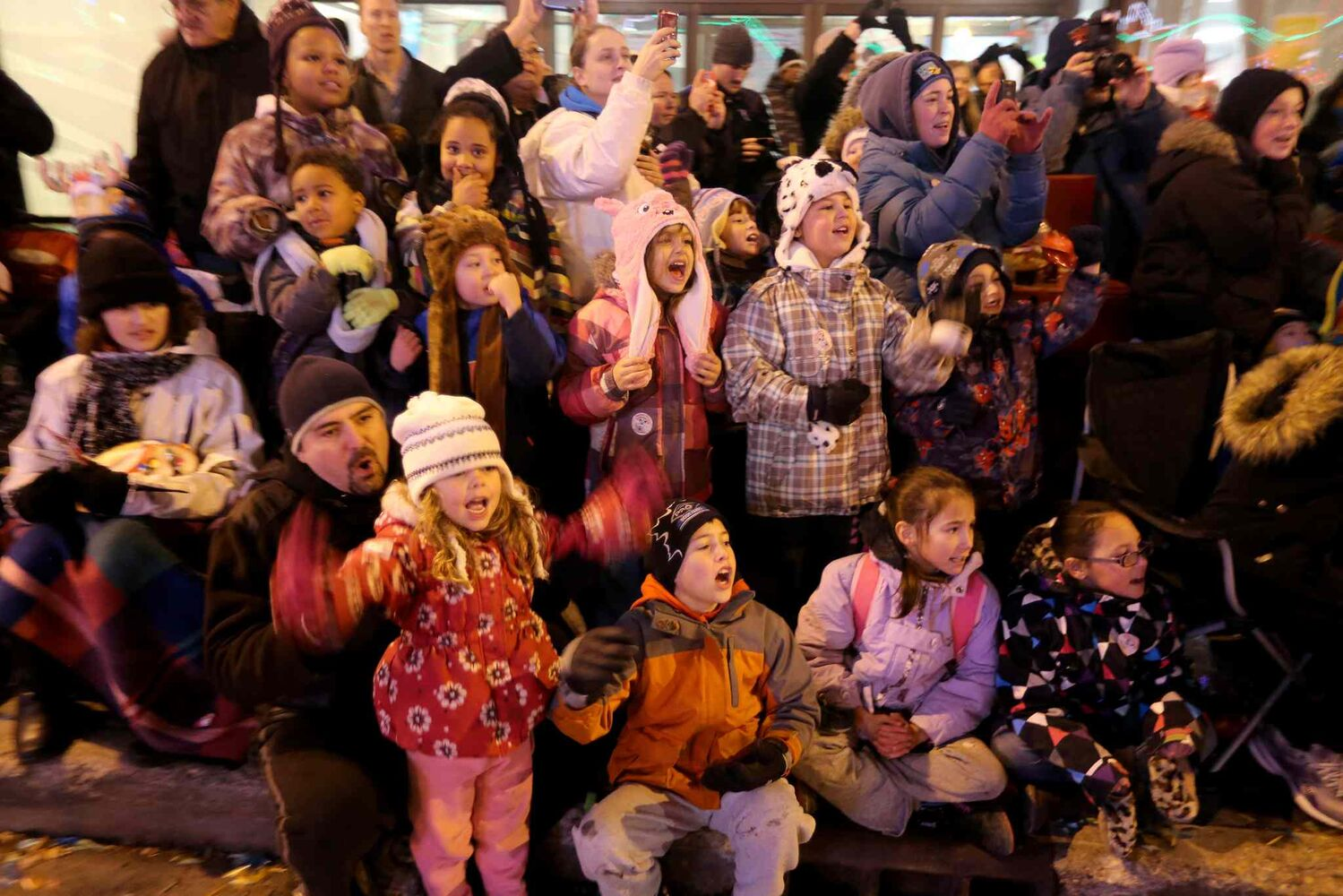 A group of adults and children wave at Santa as he passes by.