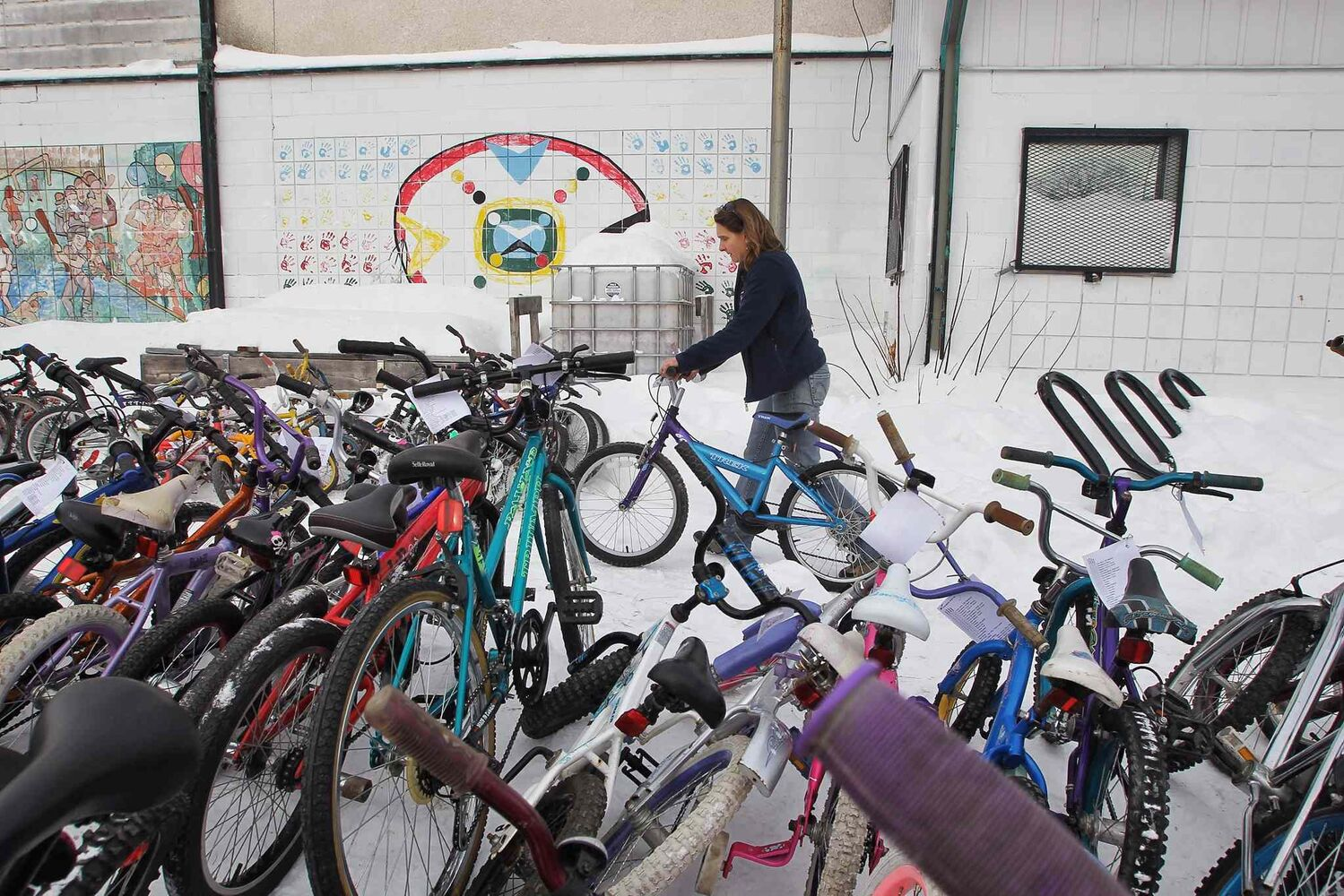 Monica Young takes one of the bikes out to the area where bikes that are ready for pick-up sit at the end of the day. (MIKE DEAL / WINNIPEG FREE PRESS)