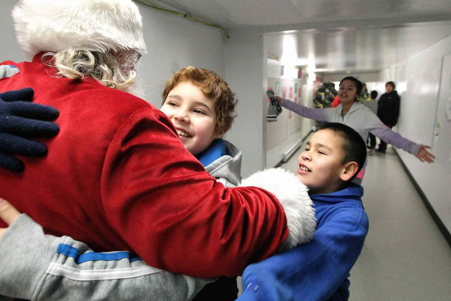 Santa greets kids at Wanipigow School on the Hollow Water First Nation after arriving with MKO Grand Chief David Harper during the Santa Express tour. (Mike Deal / Winnipeg Free Press)