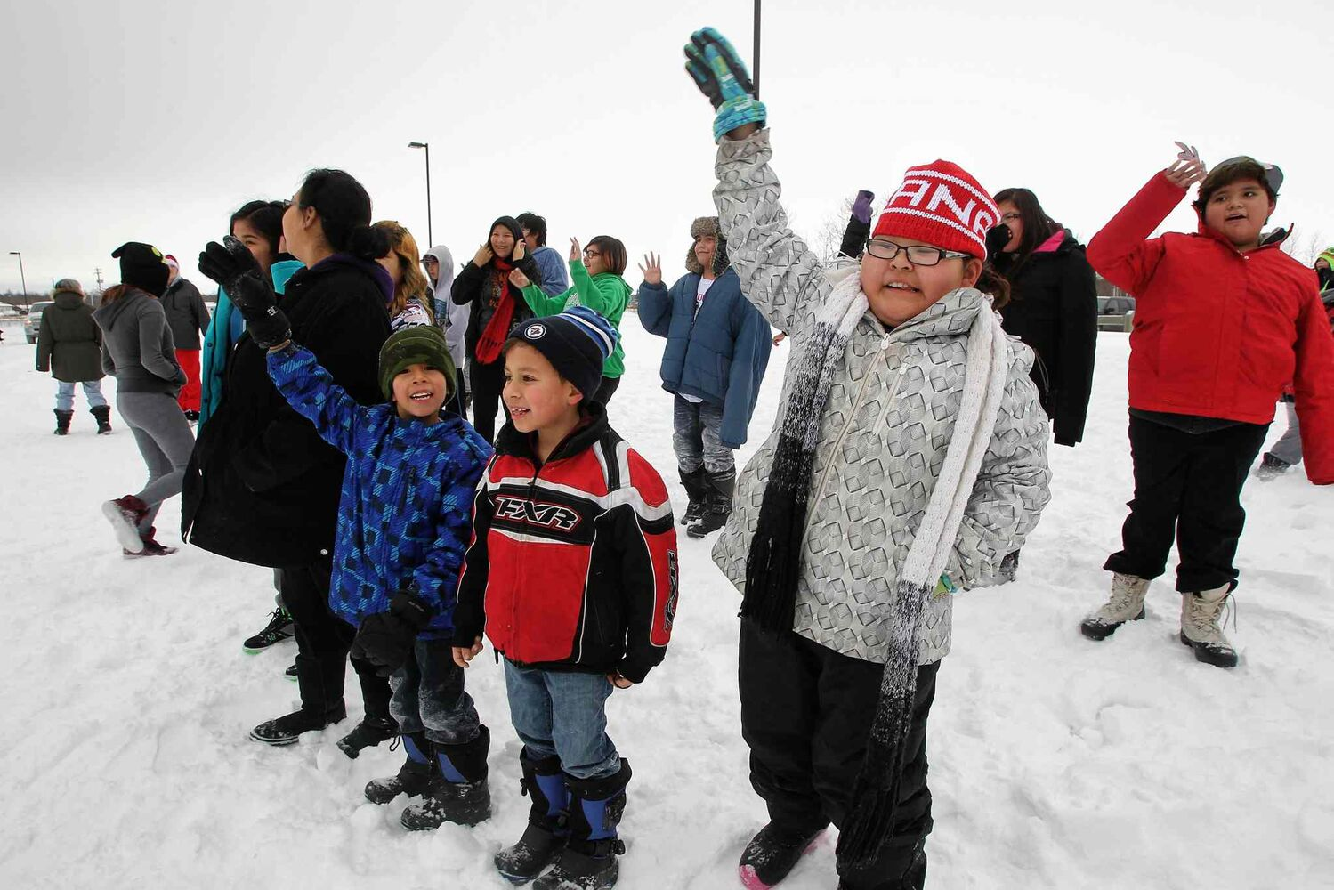 Children wave as Santa arrives by helicopter at the Black River Anishinabe School on the Little Black River First Nation with MKO Grand Chief David Harper during the Santa Express tour. (Mike Deal / Winnipeg Free Press)