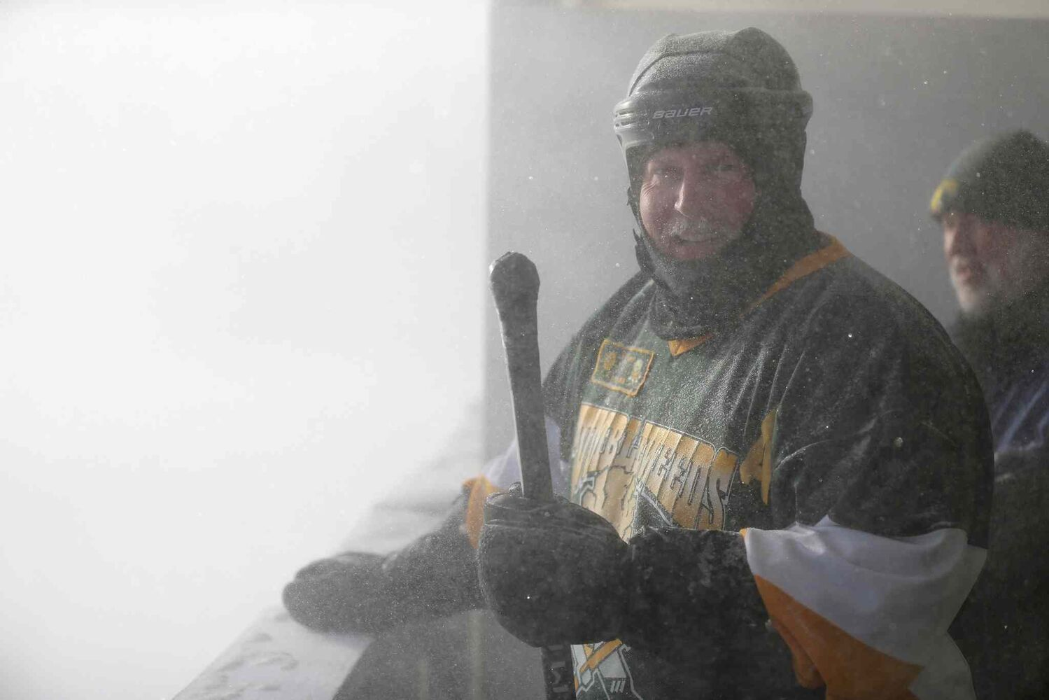 John Brennenstuhl and Cam Currie of the Tumbleweeds wait out a whiteout caused when a snowblower cleared a neighbouring ice rink during the team's spongee game against the Mighty Puckin' Drunks at Melrose Park Community Centre.
