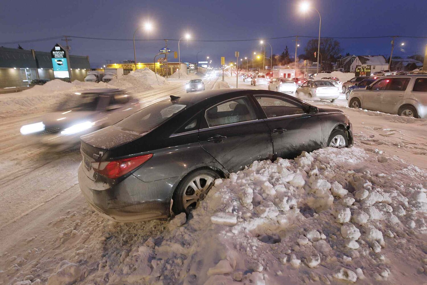 A car ended up on Century Street boulevard after sliding on the icy, rutted road on Monday. Crews continue to plow streets in extreme cold weather in southern Manitoba. ( John Woods / Winnipeg Free Press)