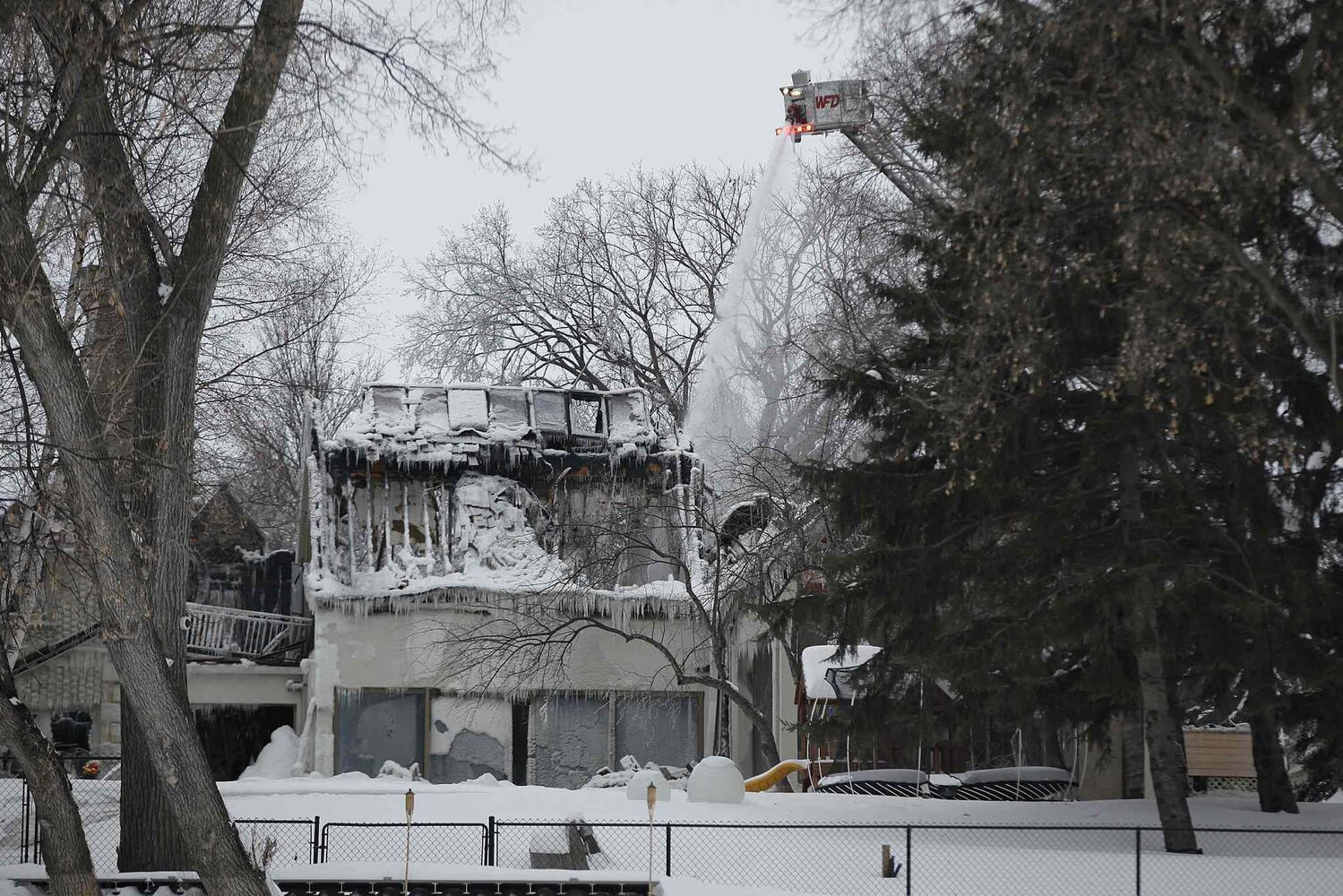 Firefighters work on extinguishing hotspots Sunday. (Winnipeg Free Press)