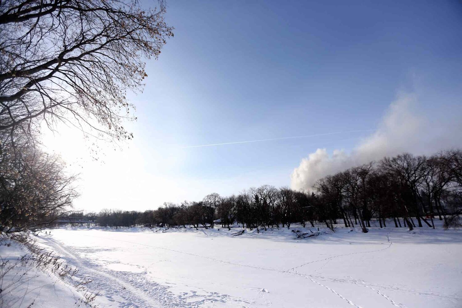 Smoke is seen from the other side of the Assiniboine River at a fire at 1021 Wellington Crescent Sunday afternoon. (Trevor Hagan / Winnipeg Free Press)