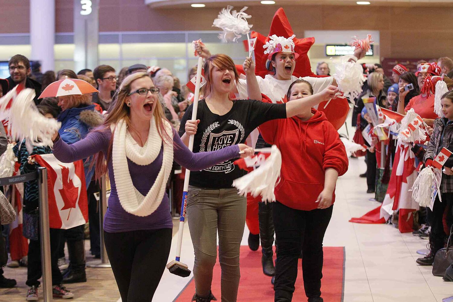 Fans get warmed up for the arrival of the Olympic curling gold medalists. (Winnipeg Free Press)