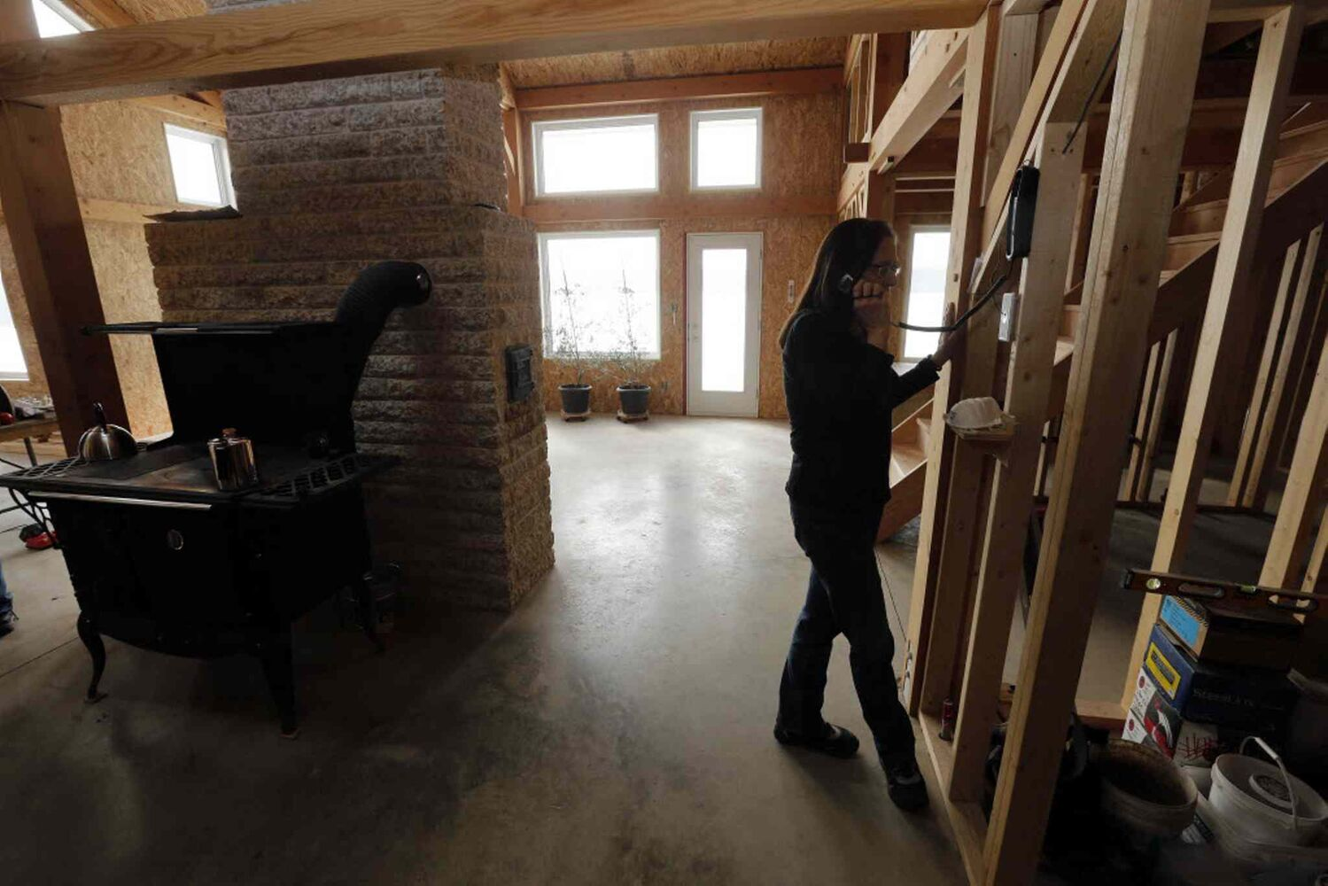 Bev Eert answers phone while coffee percolates on the wood stove in the unfinished solar home. (KEN GIGLIOTTI / WINNIPEG FREE PRESS)