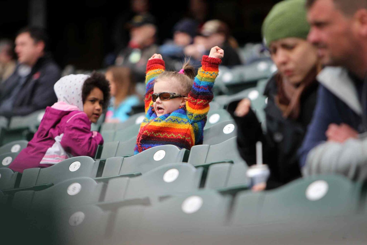 Three-year-old Ella Smith practices cheering for her home team, the Goldeyes, while hanging out in the stands Saturday.  (Ruth Bonneville / Winnipeg Free Press)