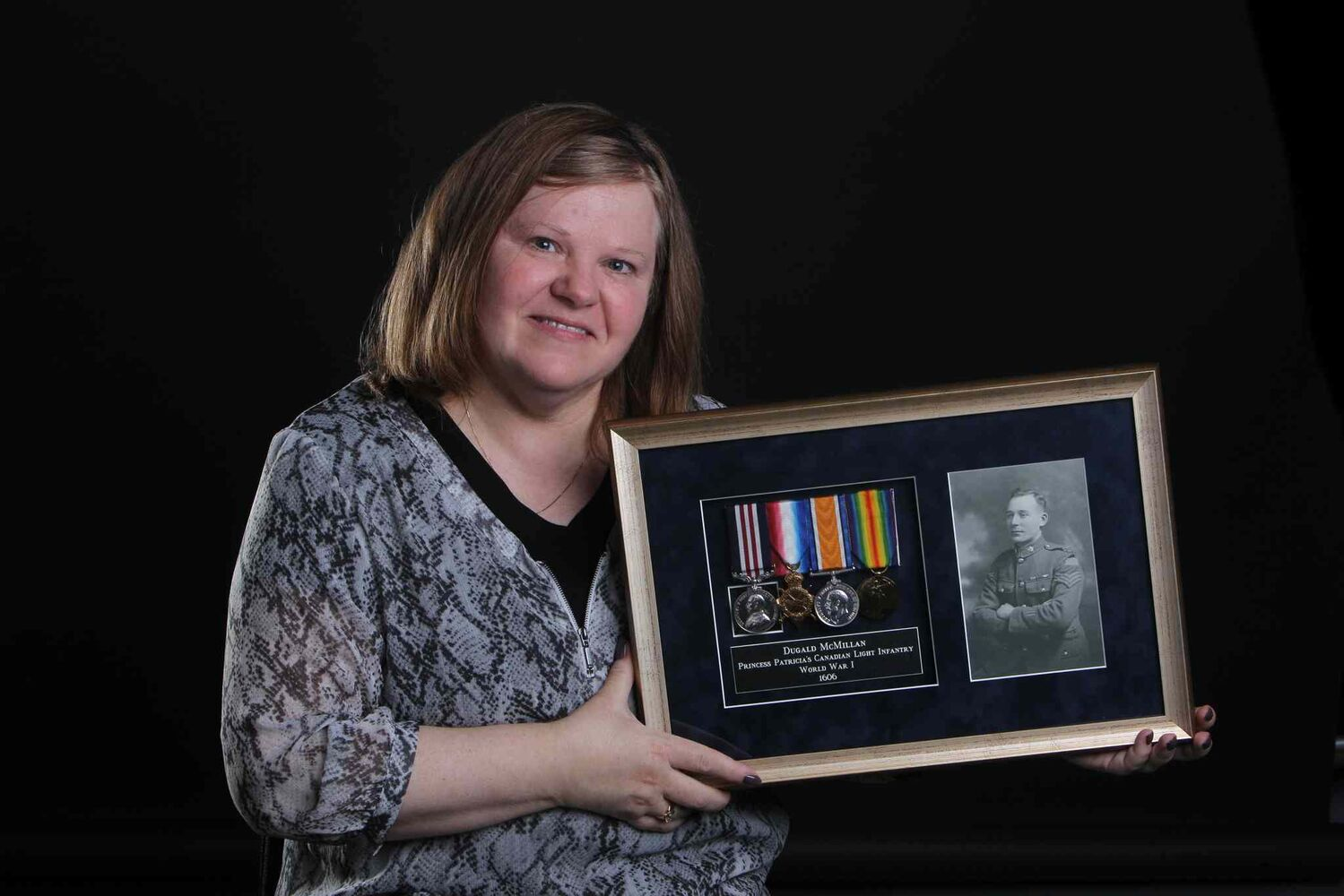 Margaret McMillan holds a photograph, medals and pay book belonging to her grandfather Dugald McMillan, with Princess Patricia's Canadian Light Infantry in the First World War. (Ruth Bonneville / Winnipeg Free Press)