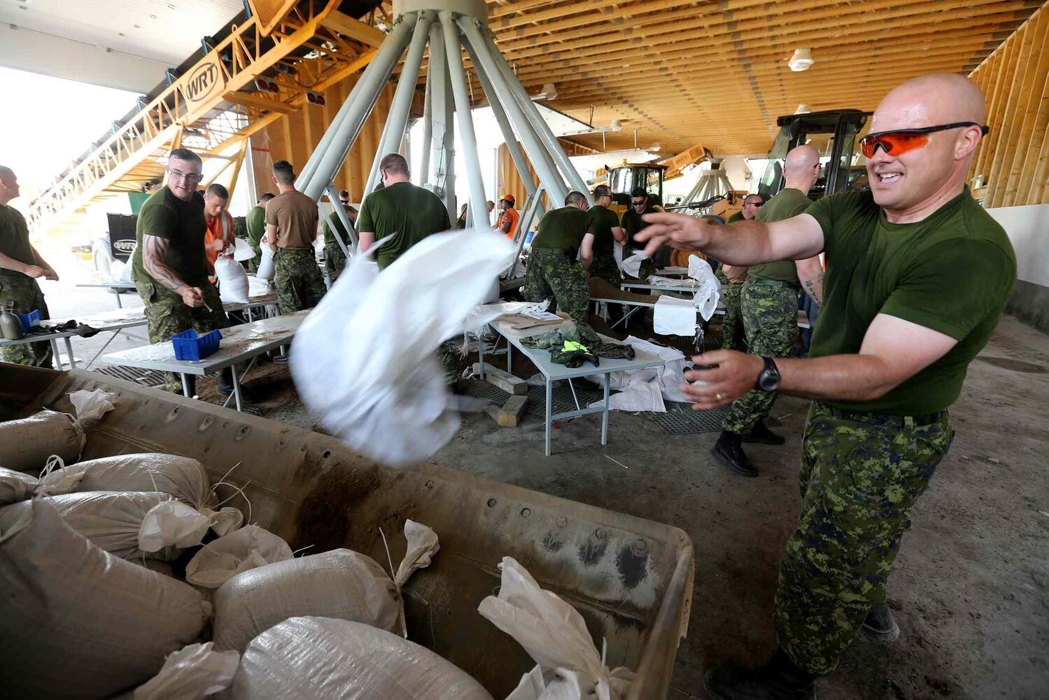 Captain Jerry Larkin, one of the soldiers from CFB Shilo, makes sandbags alongside workers from the Municipality of Portage la Prairie on Saturday.