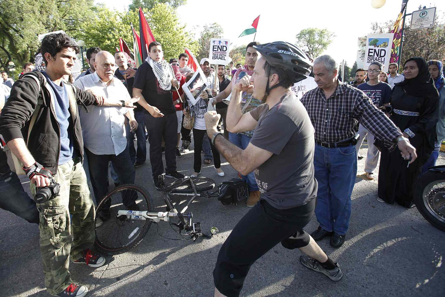 An Israel supporter cyclist provokes peaceful Palestinian supporters by yelling