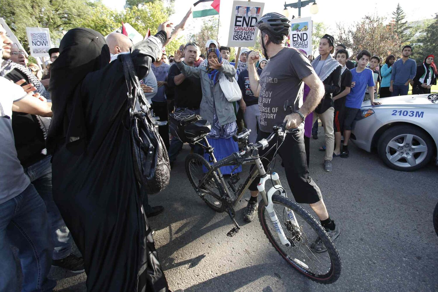 "An Israel supporter cyclist provokes peaceful Palestinian supporters by yelling ""stop hiding behind your children"" as they hold a rally at the Manitoba Legislature. (John Woods / Winnipeg Free Press)"