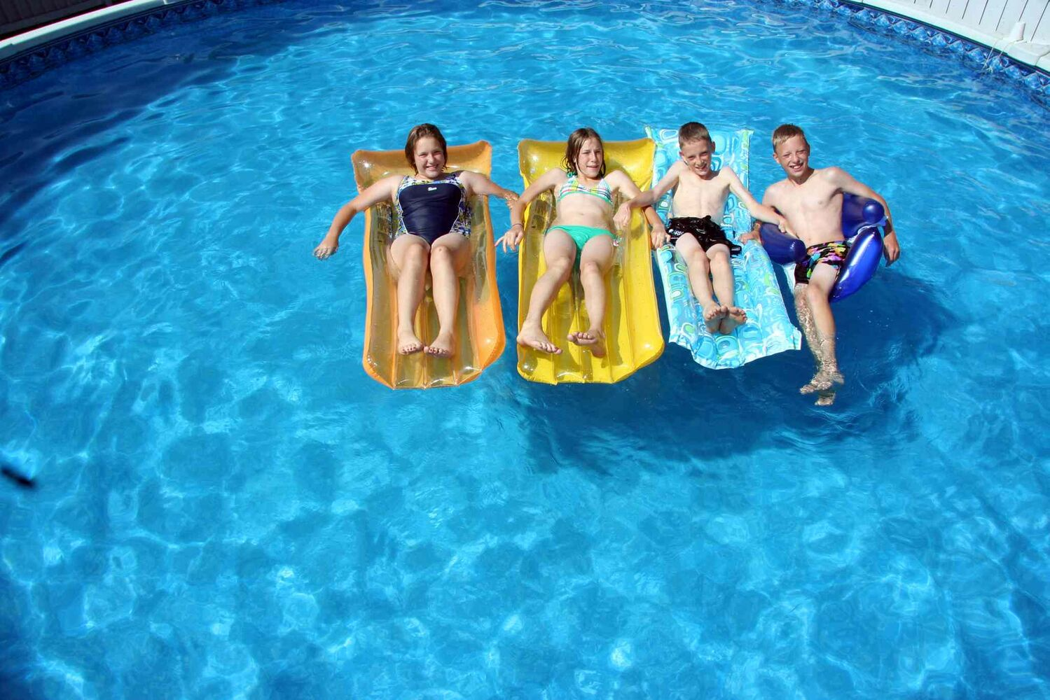 From left, Janelle Maryn, Gregory and Myles Lavich lounge in a family friend's pool in Brandon this week before their 13th birthday. (Matt Goerzen/Brandon Sun files)