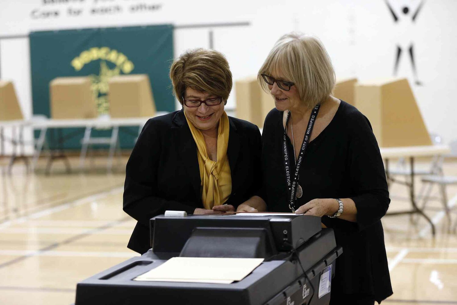 Judy Wasylycia-Leis, left, feeds her vote into a machine at Luxton School polling station. (KEN GIGLIOTTI / WINNIPEG FREE PRESS)