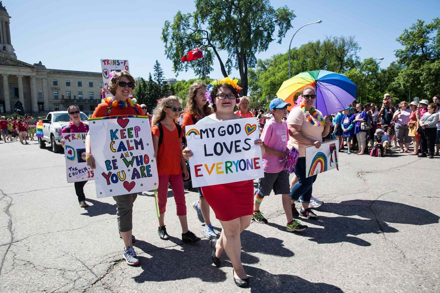 Participants display signs with inclusive messages during the 2016 Winnipeg Pride Parade. (Mike Deal / Winnipeg Free Press)